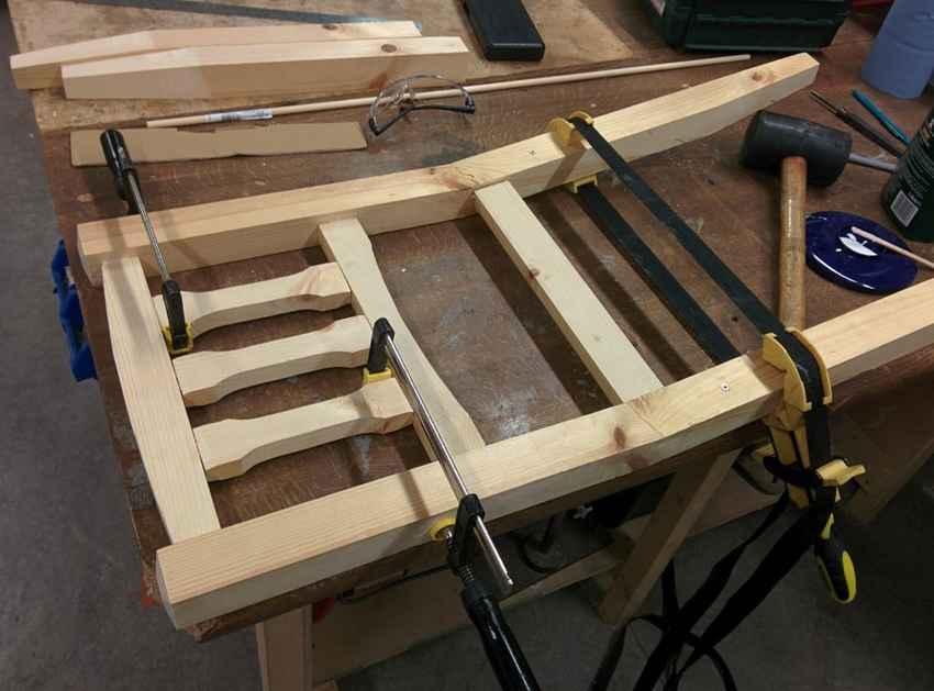Склеивание деталей стула клеем и стяжка струбцинами